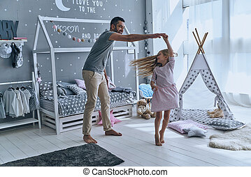 Spontaneous dance. Full length of father and daughter holding hands and smiling while dancing in bedroom