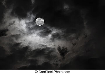 Spooky full moon and eerie white clouds against a black ...