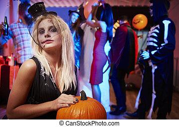 Spooky girl with orange pumpkin