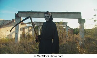 Creepy grim reaper with scythe in cloak guiding deceased soul to afterlife, turning back and gesturing to follow in rays of setting sun while walking through ruins of abandoned building on halloween.