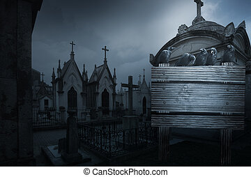 Spooky halloween background with crow, tombs in the form of chpel from an old european cemetery street and wooden placard in the foreground with an engraved skull and space to write