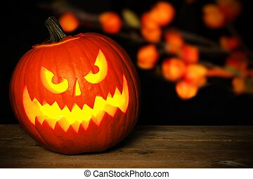 Spooky Halloween Jack o Lantern at night on wood with autumn leaves in background