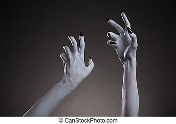 Spooky Halloween white hands with black nails stretching up