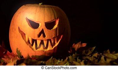 Spooky iluminated Jack O Lantern halloween pumpkin on dry leaves