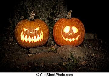 Spooky Jack-o-lanterns Outdoors - Two jack-o-lanterns sit on...