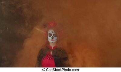 Spooky lady of dead with sugar skull and colorful wreath coming out of clouds of orange mist in rustic shed, looking with mysterious cold expression while guiding deceased to afterlife on halloween.