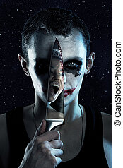 Spooky man with knife in darkness