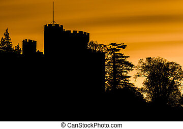 Spooky silhouette of a castle and trees with orange sky