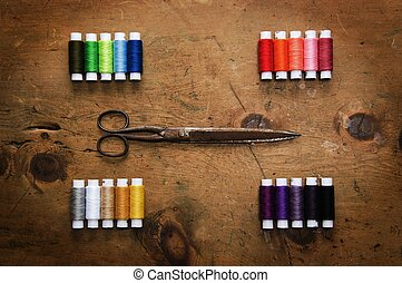 Spool colored threads and scissor - Old wood table with...