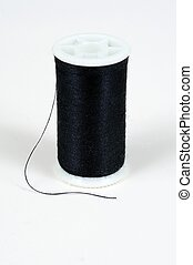 Spool of black cotton. - Spool of black cotton against a...