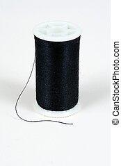 Spool of black cotton. - Spool of black cotton against a ...
