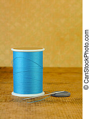 Spool of Blue Thread with a Needle and Button