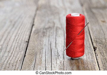 Spool of thread and needle on wooden table
