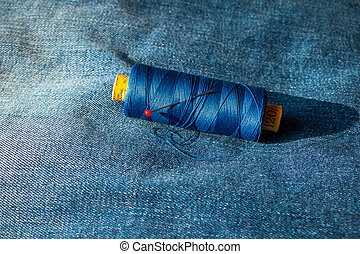 Spool of thread on a blue jeans