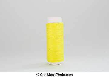 spool of yellow thread on a white background