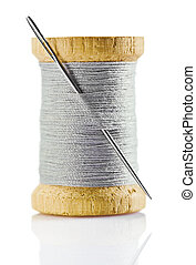 spool with gray thread and nidle