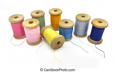 Spools of bright multi-colored threads on a white background