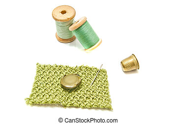 spools of green thread, button and thimble