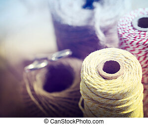 Spools of different color string with scissors