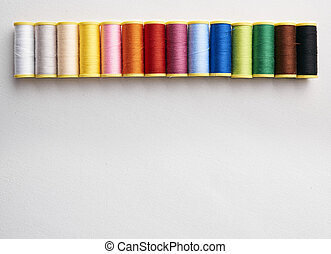 Spools of thread aligned on white cloth. Horizontal composition. Top view