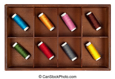Collection of different color spools of thread in a grunge wooden box. Isolated on white background