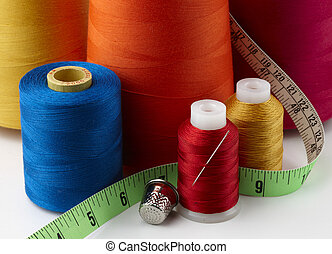 colorful spools of thread with tape measure, needle and thimble