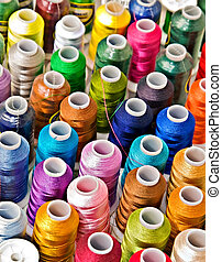 Multicolored spools of thread for a background.