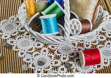 spools of thread on a wooden background