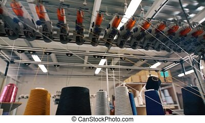 Spools of thread on knitting machine video in workshop