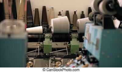 Spools of thread on knitting machine video - Spools of white...