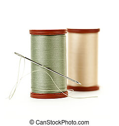 Two spools of thread with needle for sewing isolated on white background