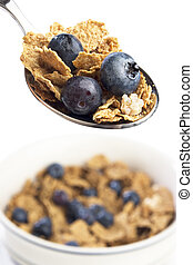 Spoon and bowl of breakfast cereal with blueberries