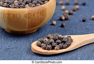 Spoon and bowl with black peppercorns