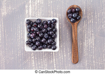 Spoon and  bowl with fresh blueberries