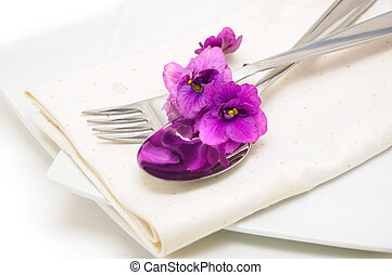 Spoon and fork on a napkin with violet close up