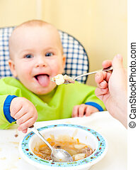Mother feeding little baby girl in a highchair, focus on spoon with food