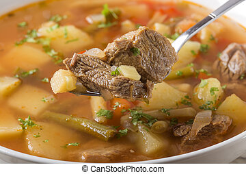 Spoon filled with vegetable beef soup