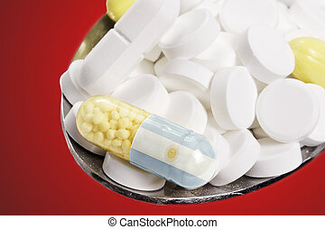 Spoon full of pills and a capsule with the flagdesign of Argentina.(series)