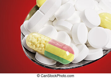 Spoon full of pills and a capsule with the flagdesign of Bolivia.(series)