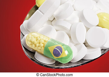 Spoon full of pills and a capsule with the flagdesign of Brazil.(series)
