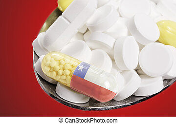 Spoon full of pills and a capsule with the flagdesign of Chile.(series)