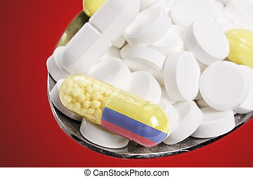 Spoon full of pills and a capsule with the flagdesign of Colombia.(series)