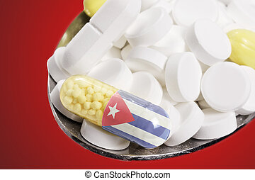 Spoon full of pills and a capsule with the flagdesign of Cuba.(series)