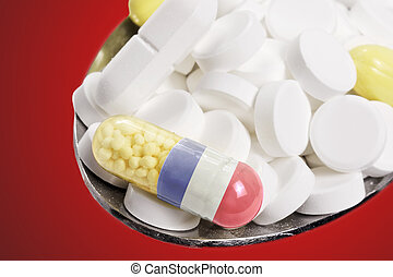 Spoon full of pills and a capsule with the flagdesign of New Caledonia.(series)