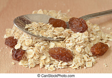 Spoon in heap of fine oat flakes and raisins