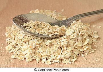 Spoon in heap of fine oat flakes