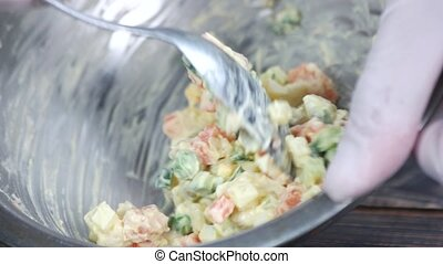 Spoon mixing olivier salad. Eggs, vegetables and mayonnaise.
