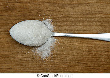 spoon of sugar on a wooden background