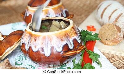 Spoon stir soup in a pot