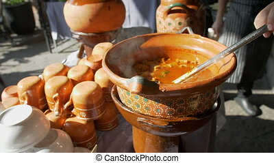 Close-up of steel spoon slowly stirring tasty-looking hot beef stew in clay pot. Smooth view of Hispanic soupy dish known as pancita on table with handmade pots and cups. Traditional Mexican cuisine